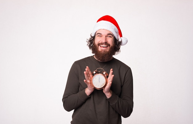 잘 생긴 수염 난 남자가 웃고 알람 시계에 크리스마스 시간임을 보여줍니다.