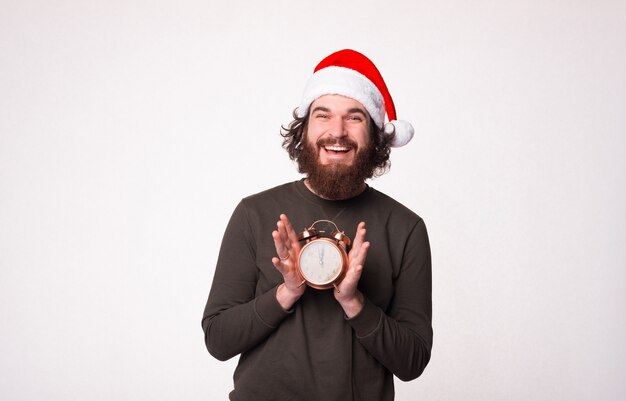 Handsome bearded man is smiling and showing that it is christmas time on an alarm clock