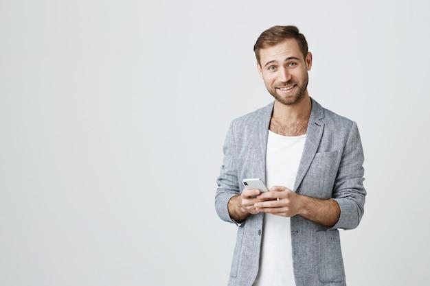 Uomo barbuto bello in giacca utilizzando il telefono cellulare