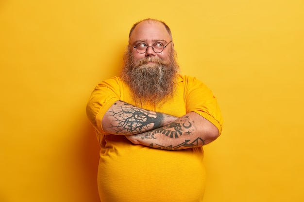 잘 생긴 수염 난 남자는 팔을 접은 채로 조심스럽게 멀리 보이며 통통한 몸매를 가지고 캐주얼 한 옷을 입고 노란색 벽 위에 고립 된 체중 감량 방법을 계획합니다. 생각에 잠겨있는 우유부단 한 사람