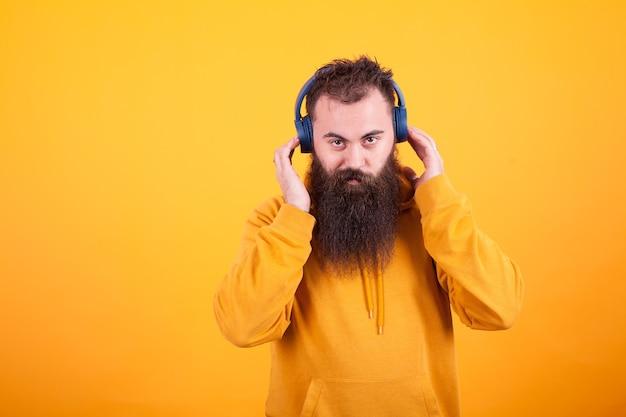 카메라를 보고 노란색 배경 위에 파란색 헤드폰에 음악을 듣고 잘생긴 수염된 남자. 멋진 노래. 노란색 후드티.