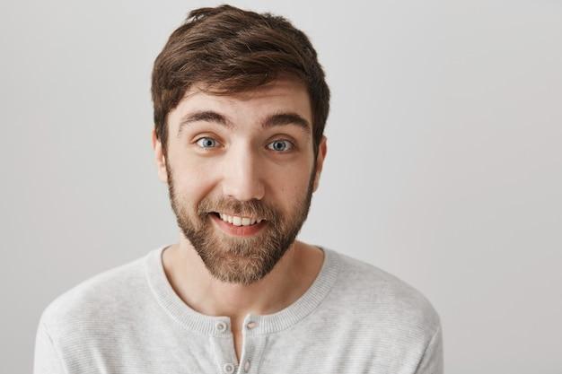 Красивый бородатый мужчина выглядит заинтригованным и улыбается