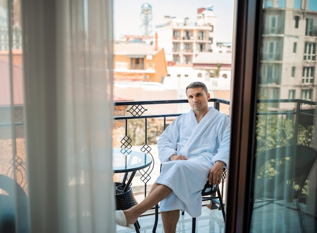 Handsome bearded man in the morning sitting in a hotel room in a robe. young man wearing white bathrobe after shower bath. gygiene concept