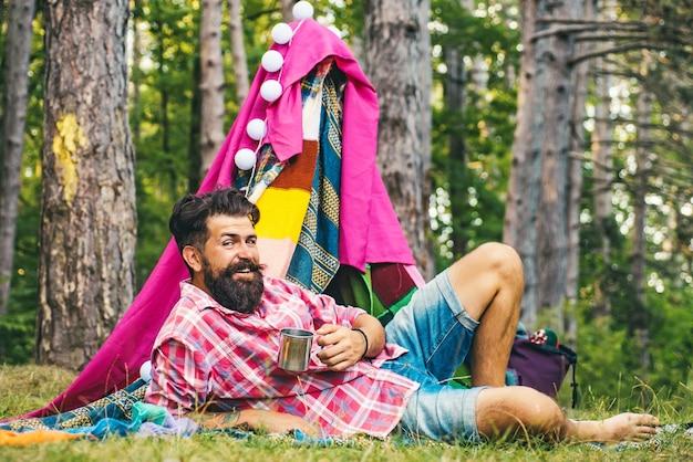キャンプテントの横にあるハンサムなひげを生やした男