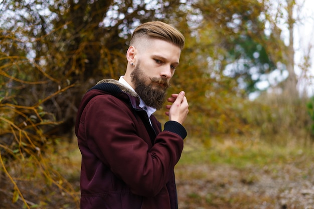 잘 생긴 수염 난 남자 야외 초상화는 공원에서 가을 자연의 배경에 서...