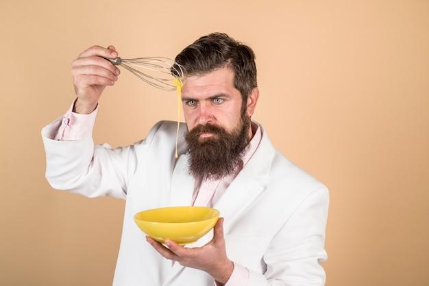 朝食の卵を準備するハンサムなひげを生やした男ボウルと卵泡立て器のキッチンツールでひげを生やした男