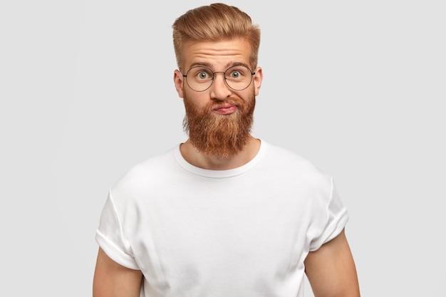 ハンサムなひげを生やした男は、予期しないニュースを受け取るために驚いて困惑し、ためらいで唇を財布に入れます