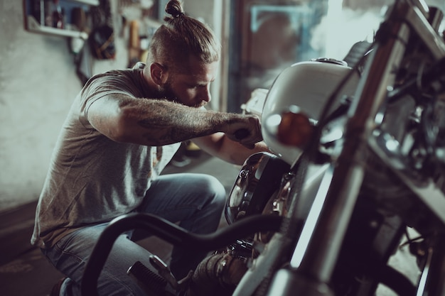 Handsome bearded man repairing his motorcycle in the garage. a man wearing jeans and a t-shirt