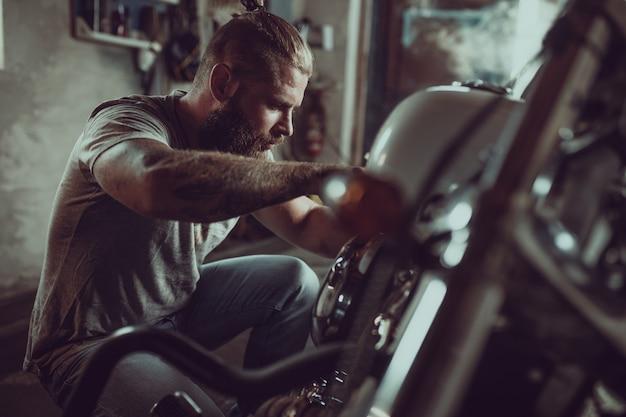 Красивый бородатый человек, ремонт своего мотоцикла в гараже. мужчина в джинсах и футболке