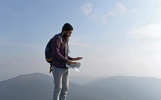 Handsome bearded man running on mountain hipster with beard and moustache runs on mountain top on sunny summer day