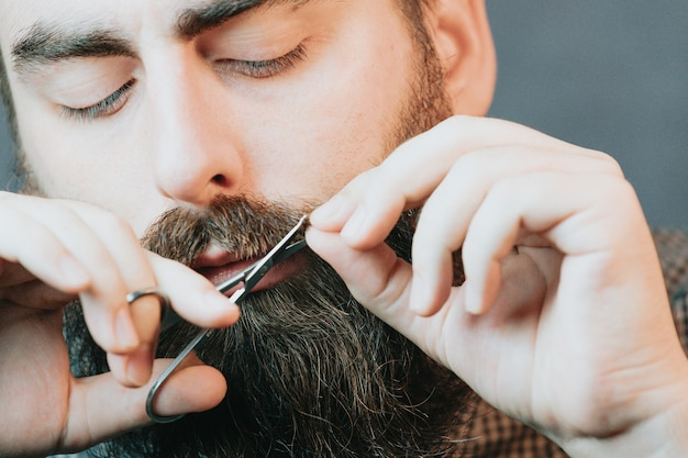Handsome bearded man shaving his beard, young caucasian bearded man trimming beard in home during quarantine. lifestyle concept.