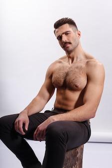 ハンサムなひげを生やした男、上半身裸、白い背景の上の木の幹に座っている筋肉質のボディ、上腕二頭筋、上腕三頭筋を示しています。垂直ビュー。