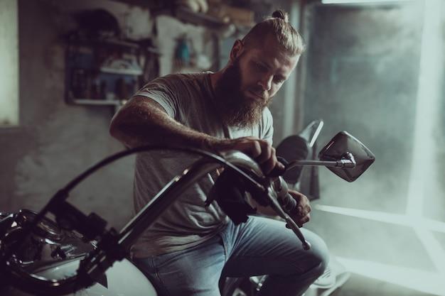 Красивый бородатый мужчина сидит на сиденье мотоцикла и ремонтирует руль
