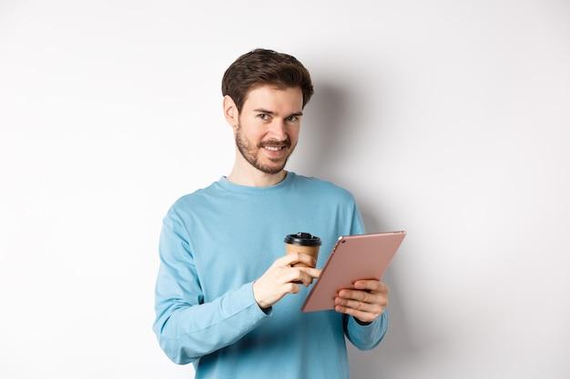 카메라를 보며 웃고 있는 잘생긴 수염난 남자, 커피를 마시고 디지털 태블릿을 읽고 흰색 배경 위에 서 있는 남자