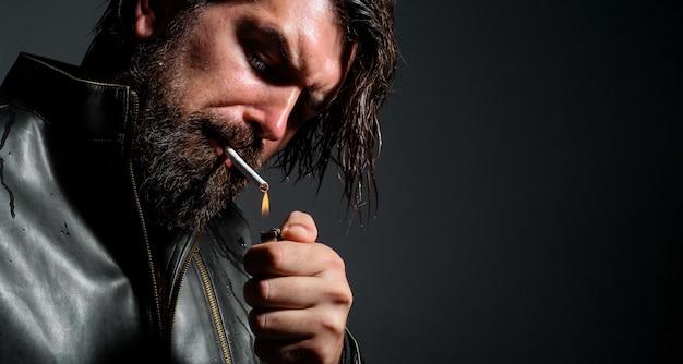 잘생긴 수염 난된 남자 흡연 담배입니다. 라이터와 담배가 있는 세련된 힙스터. 확대.