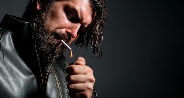 Handsome bearded man smoking cigarette. stylish hipster with lighter and cigarette. closeup.