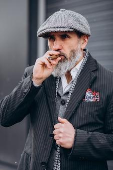 Bell'uomo barbuto che fuma sigaretta