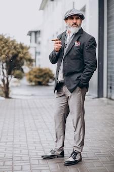 ハンサムなひげを生やした男がタバコを吸う