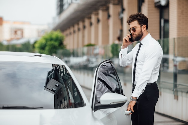 Handsome bearded man speaking by phone and entering his car while standing outdoors on the streets of the city near the modern office center