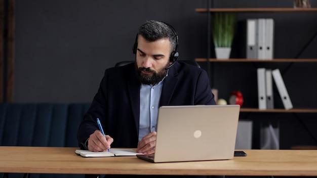 Красивый бородатый мужчина учится онлайн с помощью веб-камеры ноутбука, писать лекцию в ноутбуке. онлайн-образование, удаленная работа, домашнее образование.