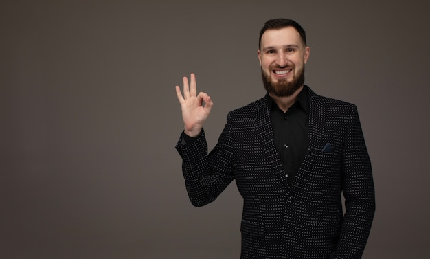 Handsome bearded man in suit shows ok sign. cool man doing okay symbol. business success concept.