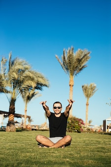 Uomo barbuto bello in occhiali da sole che si siede sull'erba verde e rilassarsi godersi le vacanze estive con le mani alzate in alto sorriso felice.