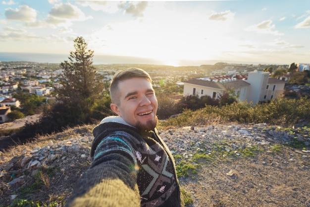 셀카를 찍는 잘생긴 수염난 남자. 행복한 학생은 자신의 블로그에 재미있는 사진을 만듭니다.