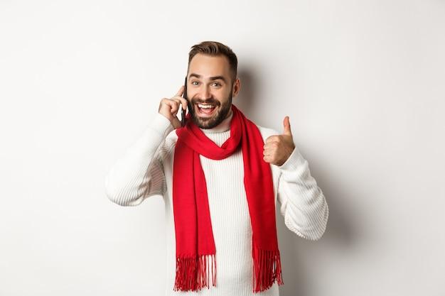 Bell'uomo barbuto che parla al telefono, mostra i pollici in su in segno di approvazione, come qualcosa, conferma l'ordine, in piedi su sfondo bianco
