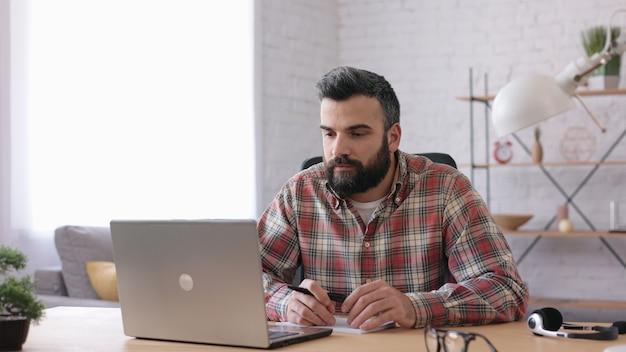 수염난 잘생긴 남자가 노트북 웹 카메라와 온라인으로 대화를 가르칩니다. 온라인 교육, 원격 근무.