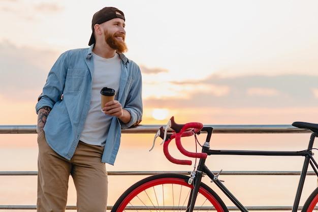 コーヒーを飲みながら朝日、自転車で旅行するハンサムなひげを生やした男、健康的なアクティブなライフスタイルの旅行者