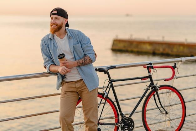 Красивый бородатый мужчина, путешествующий с велосипедом в утреннем восходе солнца у моря, пьет кофе, путешественник здорового активного образа жизни