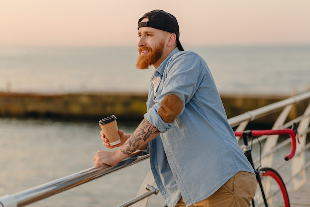 Handsome bearded man traveling with bicycle in morning sunrise by the sea drinking coffee, healthy active lifestyle traveler