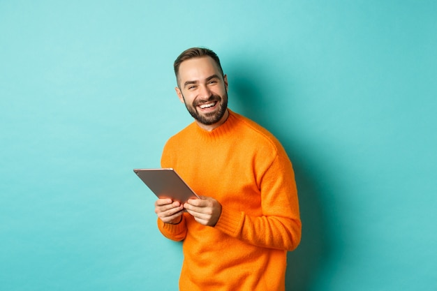 Красивый бородатый мужчина с помощью цифрового планшета, смеясь над камерой, счастлив, стоя на голубом фоне.