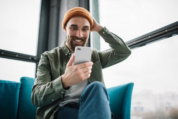 Красивый бородатый мужчина с помощью смартфона и мобильного приложения для онлайн-покупок, заказа еды