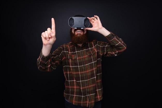 Vrメガネを使用して、暗い壁の上の何かに触れようとしているハンサムなひげを生やした男