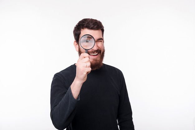Handsome bearded man watching you through a magnifying glass on white space.