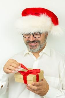 Красивый бородатый мужчина в новогодней шапке держит подарочную коробку с красной лентой