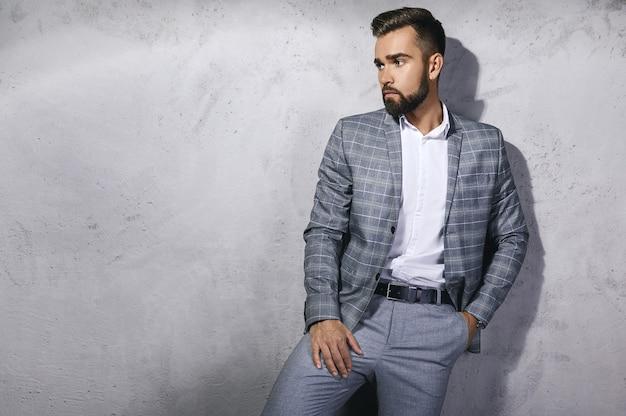 회색 체크 무늬 양복을 입고 잘 생긴 수염 난된 남자는 콘크리트 벽에 포즈