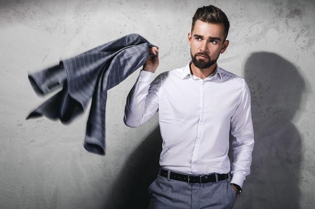 Красивый бородатый мужчина в сером костюме позирует у бетонной стены