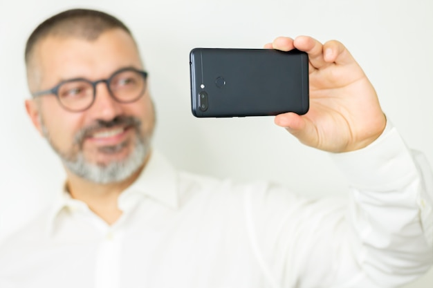 Красивый бородатый мужчина в рубашке и очках, делающий селфи или общающийся в интернете