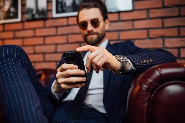 スマートフォンを保持している革のソファに座ってスーツを着ているハンサムなひげを生やした男。快適さとリラクゼーション。