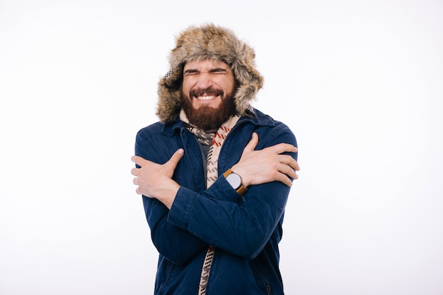 冬の服を着ているハンサムなひげを生やした男は、寒い冬の天候をすくめています。
