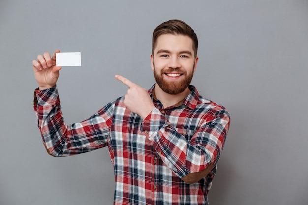 Uomo barbuto bello con il biglietto da visita in bianco