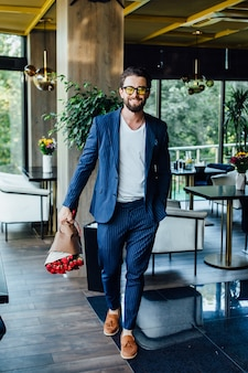 Handsome bearded man with bouquet red roses coming in restaurant