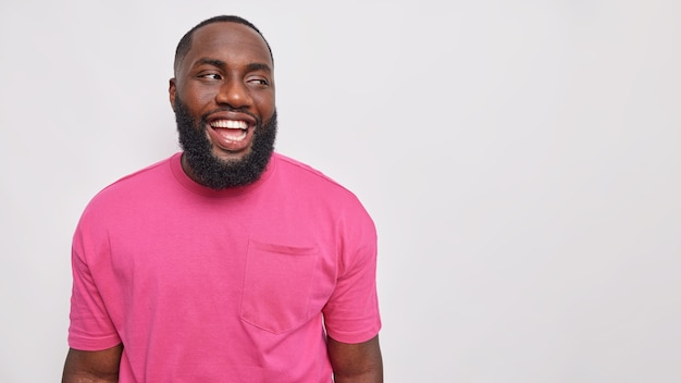 Handsome bearded man with dressed in casual pink t shirt laughs carefree shows optimism poses against grey studio wall