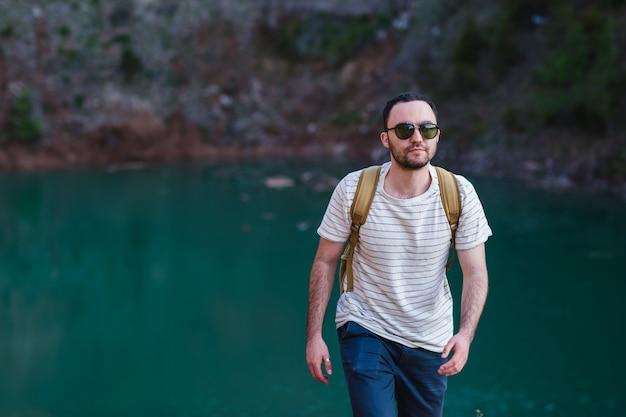 ハンサムなひげを生やした男。ポケットに手を入れて、湖の近くに立っています。サングラスとファッショナブルな服を着ている若い男