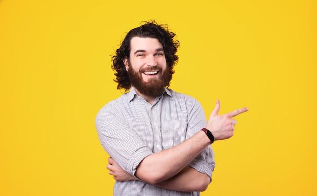 Красивый бородатый мужчина с длинными вьющимися волосами улыбается и указывает в сторону