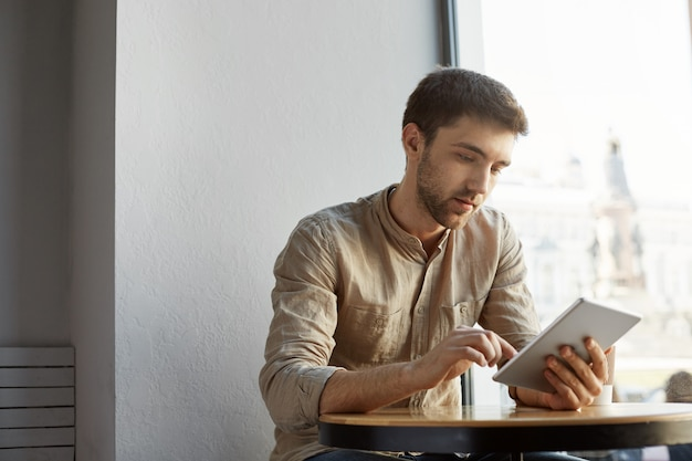 Handsome bearded man with short hair in casual clothes sitting in cafe, looking through startup project details on tablet. business concept.