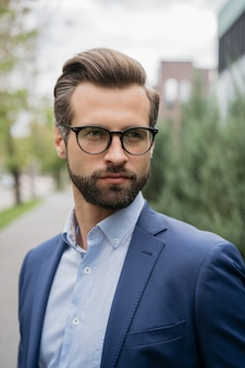 Красивый бородатый мужчина со стильными волосами в очках делового костюма смотрит на улицу