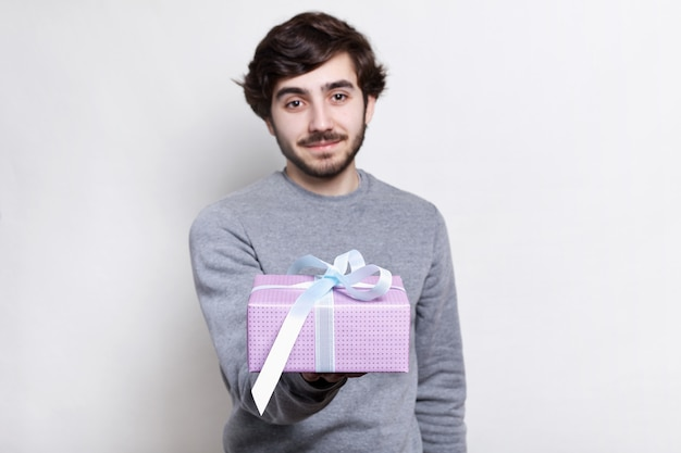 Handsome bearded man with trendy hairstyle and beard dressed in grey sweater holding a present in his hand.